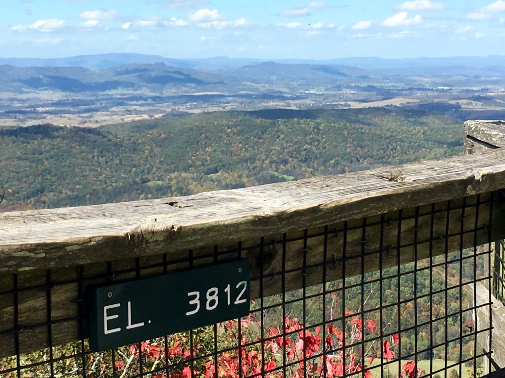 Deck railing with sign that says EL 3812 with mountains in the distance and blue skies with white clouds