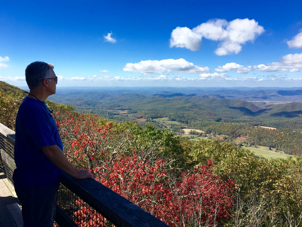 Man in blue shirt standing in shadow at deck railing looking over colorful trees and mountains in the distance with blue skies and white clouds