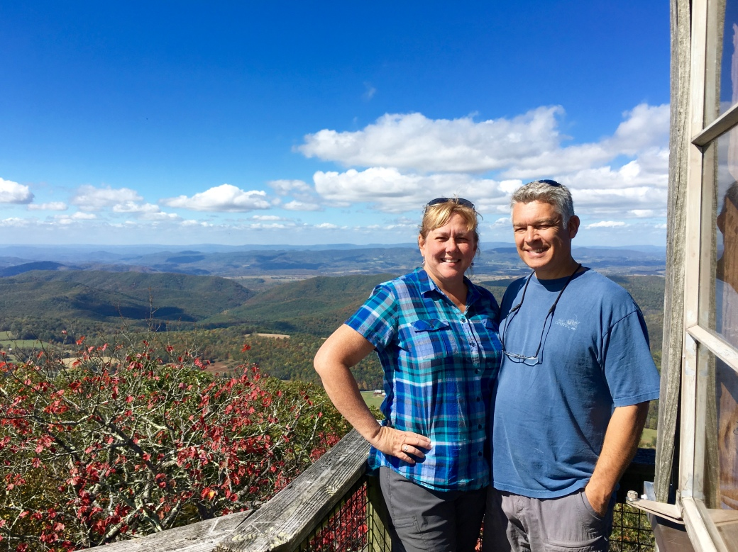 Squinting man and woman in blue facing camera on deck of fire tower with tops of mountains, trees, and blue sky with white clouds in background