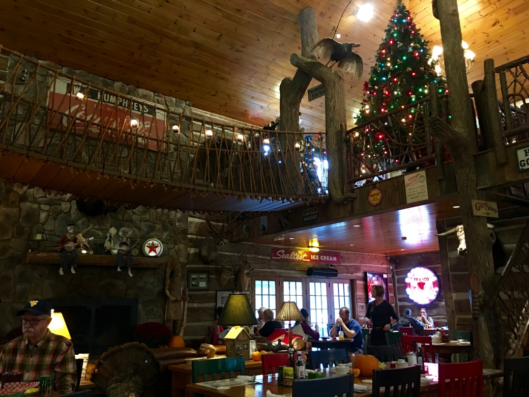 Inside of open two story building with bridge across the middle of room, a christmas tree, taxidermy animals, old Texaco signs, people sitting at tables, log walls