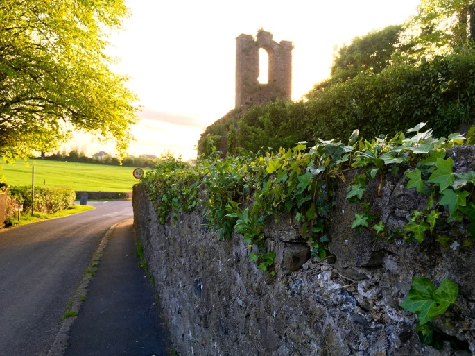 stone wall with green ivy, country road, church ruins