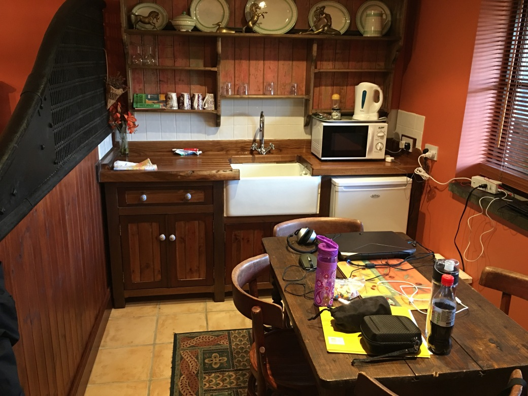 a small kitchen with a table and four chairs, a sink, wooden cabinets, a dorm sized refrigerator and a microwave