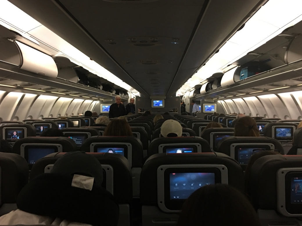 View of the inside of a large airplane about half way back with 8 seats across